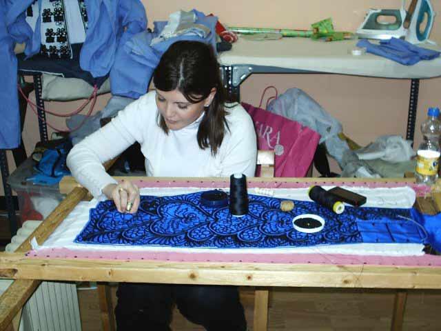 La bordadora aguja en mano bordando una taleguilla