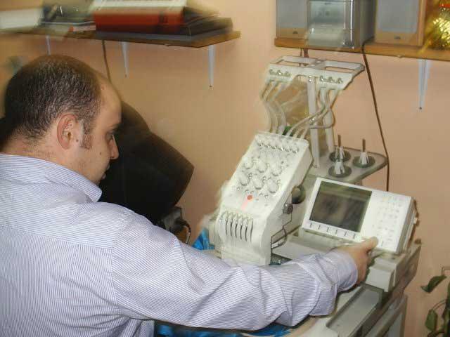 Pedro señala en la máquina el tipo de bordado que habrá de ejecutar.