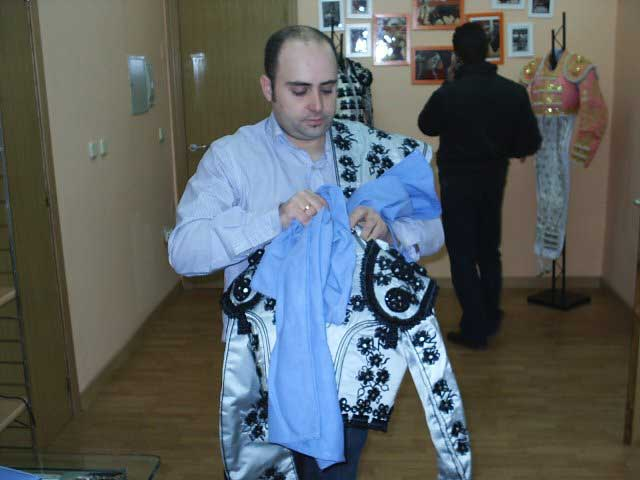 Las manos de Pedro dan los últimos retoques antes de colocar el traje en su percha.