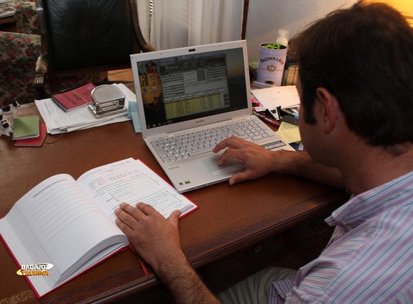 Carlos Muñoz consultando datos en el ordenador y los libros