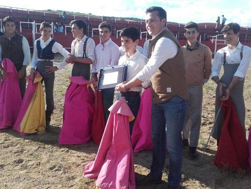 El alumno de la escuela taurina de Badajoz recogiendo el trofeo que le acredita como ganador del Bolsín Dehesa y Toro de Táliga