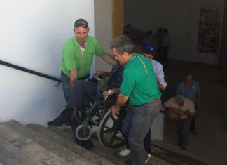 Dos miembros del personal de plaza y un aficionado suben a una persona por las escaleras hasta el palco de movilidad reducida ante la falta del elevador mecánico