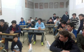 Los niños de la escuela junto a su maestro Luis Reina atentos a las explicaciones de Tomás Martínez
