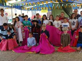 Los niños que asistieron al toreo de salón posando junto a los útiles de tauromaquia